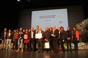 Eles et agents municipaux sur scène pour recevoir la 3ème fleur du label VVF