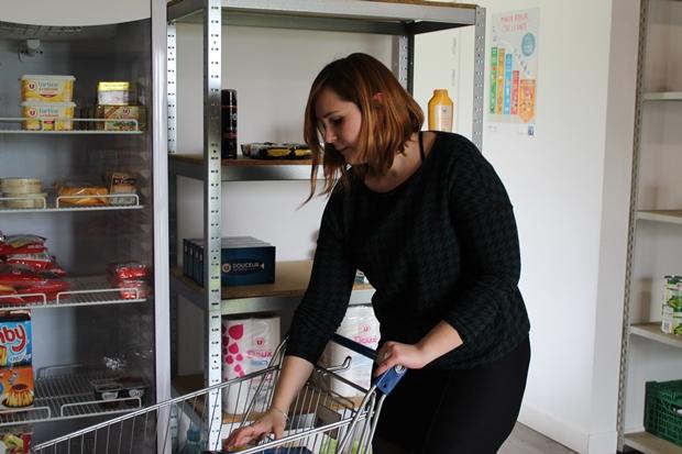 Cécile Lebrun, conseillère en économie sociale et familiale au CCAS, dispose les produits sur les rayonnages du Marché solidaire